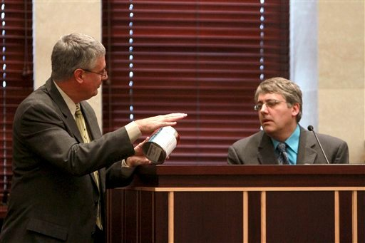 Assistant state attorney Jeff Ashton, left, holding a can of evidence, talks with Dr. Arpad Vass of the Oak Ridge National Laboratory during the Casey Anthony trial at the Orange County Courthouse on Tuesday, June 7, 2011, in Orlando, Fla.