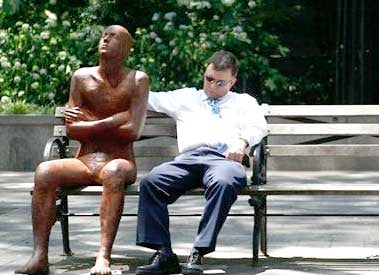 A man takes a nap on a shady park bench next to a sculpture in Dag Hammarskjold Plaza, Wednesday, June 8, 2011 in New York.