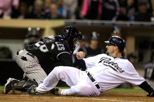 San Diego Padres' Kyle Phillips slides past Colorado Rockies catcher Jose Morales while scoring in the fifth inning of a baseball game Tuesday, June 7, 2011 in San Diego. (AP Photo/Lenny Ignelzi)
