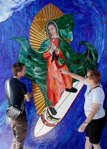 In this May 27, 2011 photo, Anthea Beletsis, right, of Encinitas, Calif., and Jules Itzkoff, of Cincinatti, Ohio, look at an image of the Virgin of Guadalupe riding a surfboard that hangs under a train bridge in Encinitas, Calif.