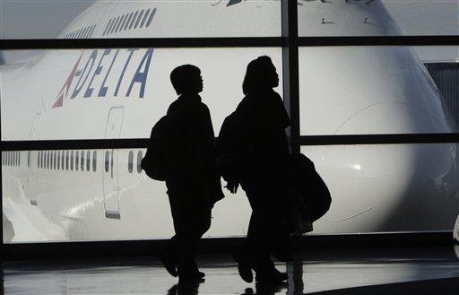 FILE - In this Jan. 21, 2010 file photo, passengers walk past a Delta Airlines 747 aircraft in McNamara Terminal at Detroit Metropolitan Wayne County Airport in Romulus, Mich.