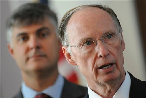 Sen. Scott Beason R-Gardendale, left, listens as Alabama Gov. Robert Bentley speaks before signing into law what's being called the strongest bill in the nation cracking down on illegal immigration. (AP Photo/Montgomery Advertiser, Mickey Welsh)