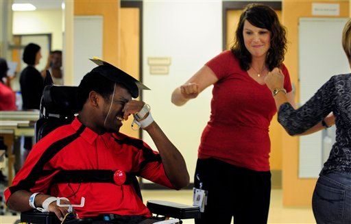 Therapist Erin Smith, center, and counselor Cheryl Linden shake their hips in a celebratory dance for University of Georgia baseball player Johnathan Taylor as he graduates from the Shepherd Center in Atlanta on Tuesday May 24, 2011.