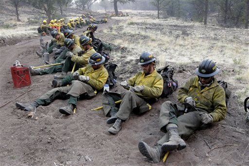 Fire crew members sharpen their tools as they prepare for a back burn operation in Eagar, Ariz., Wednesday, June 8, 2011.