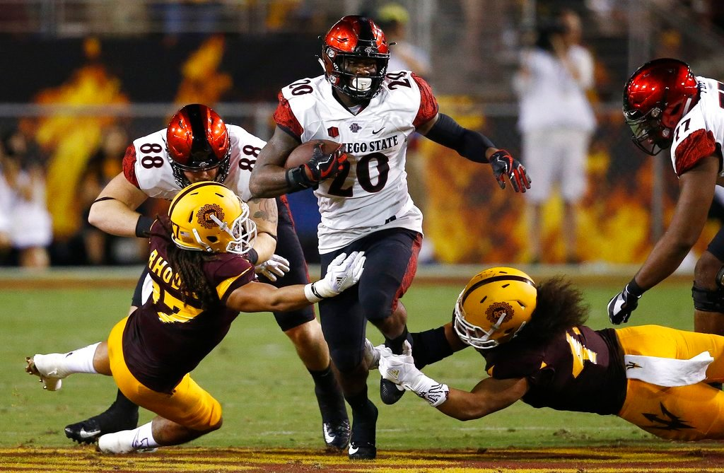 San Diego State's Rashaad Penny runs with the ball as Arizona State's J'Marcus Rhodes, left, and Alani Latu, right, move in to make the tackle as San Diego State's David Wells (88) tries to block Rhodes (AP Photo/Ross D. Franklin)