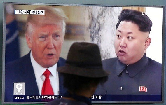 A man watches a television screen showing U.S. President Donald Trump and North Korean leader Kim Jong Un.