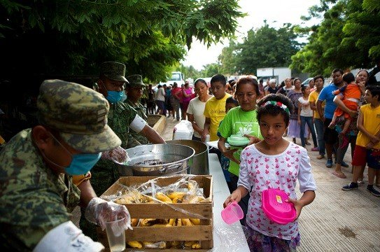 Soldiers serve breakfast to people sheltering at a technology school after their homes were destroyed.
