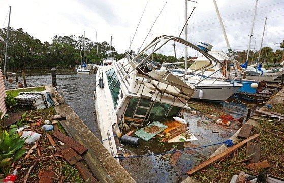A sinking boat is surrounded by debris in the aftermath of Hurricane Irma at Sundance Marine in Palm Shores, Fla.