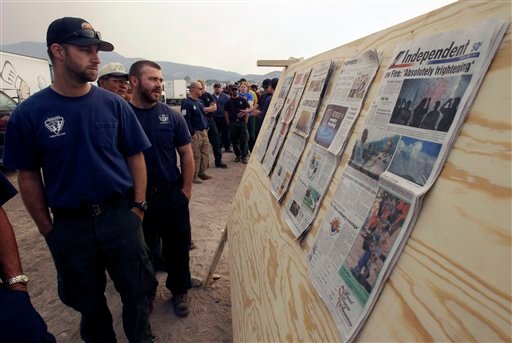 Firefighters read press clippings about the Wallow Fire as they wait for a meal at an incident command center in Eagar, Ariz., Thursday, June 9, 2011.
