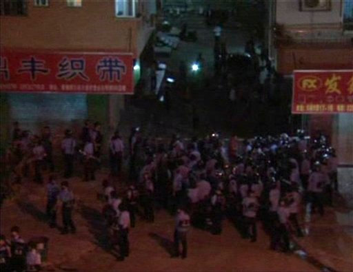 In this Sunday, June 12, 2011 image made from video broadcast by Cable TV, helmeted anti-riot police officers try to arrest protesters in Xintang, in southern China's Guangdong Province. (AP)