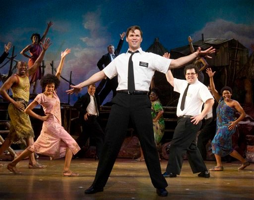"In this theater publicity image released by Boneau/Bryan-Brown, Andrew Rannells, center, performs with an ensemble cast in ""The Book of Mormon"" at the Eugene O'Neill Theatre in New York."
