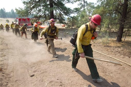 Firefighter Justin Needles, front right, of the Red Rock Interagency Crew out of Moab, Utah, and other firefighters walk towards an area to fight the Wallow Fire in Luna, , N.M. on Friday, June 10, 2011.