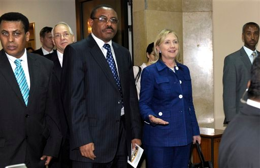 Secretary of State Hillary Rodham Clinton walks out of her meeting with Ethiopia's Prime Minister Meles Zenawi, center, at the Prime Minister's compound in Addis Ababa, Ethiopia, Monday, June 13, 2011.