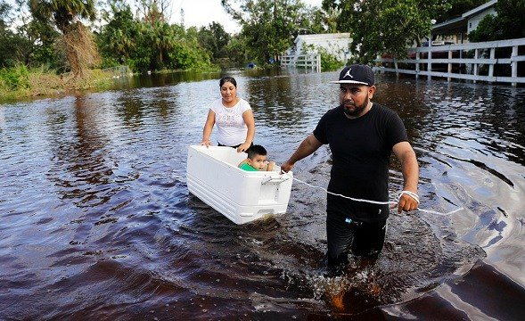 Alfonso Jose pulls his son Alfonso Jr., 2, in a cooler with his wife Cristina Ventura as they wade through their flooded street.