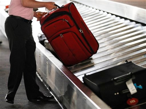 A traveler collects his bag from a luggage carousel in the Philadelphia International Airport Monday, June 13, 2011, in Philadelphia.