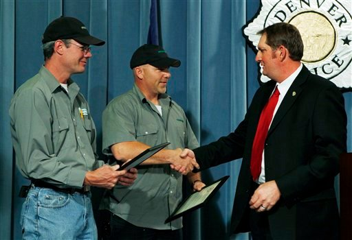 Frontier Airlines employees Mark Adams, left, and Kris Musil are congratulated by Detective Ed David during a news conference at Denver Police headquarters on Tuesday, June 14, 2011.