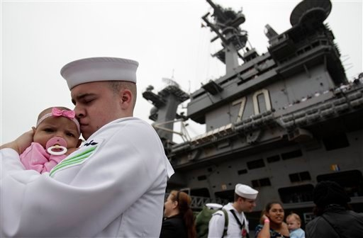 Seaman Quincy Fermer of the USS Carl Vinson hugs his four-month-old daughter Thiana after seeing her for the first time after disembarking from the aircraft carrier USS Carl Vinson Wednesday, June 15, 2011, in San Diego.