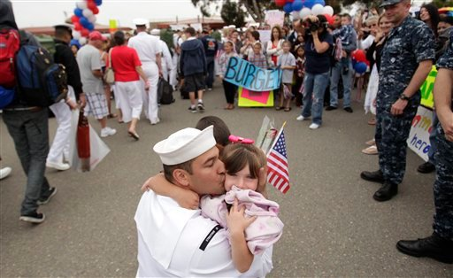 Navy Petty Officer First Class Mitchell Gallego hugs his two daughters after disembarking from the aircraft carrier USS Carl Vinson.
