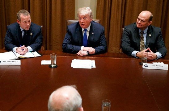 Rep. Josh Gottheimer, D-N.J., left, and Rep. Tom Reed, R-N.Y., right, listen as President Donald Trump speaks during a meeting with a bipartisan group of lawmakers.
