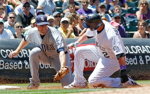 Colorado Rockies Troy Tulowitzki, right, is tagged out by San Diego Padres third baseman Chase Headley as Troy Tulowitzki tried to advance to third on an a ground ball during the second inning of a baseball game at Coors Field in Denver on Wednesday, June