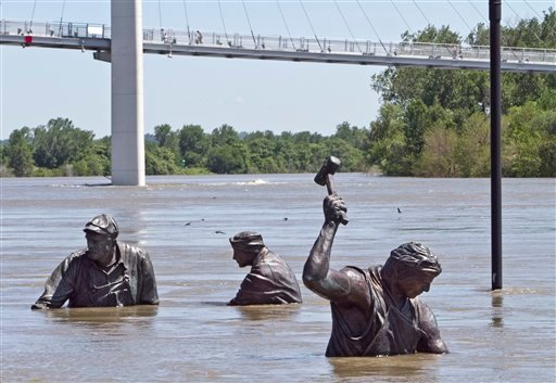 Statues of workers of various trades, part of the Monument for Labor by Matthew J. Placzek, stand in the rising waters of the Missouri River, in Omaha, Neb., Wednesday, June 15, 2011. (AP Photo/Nati Harnik)