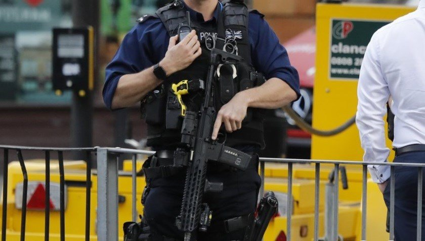 An armed police officer stands nearby after an incident on a tube train at Parsons Green subway station in London.