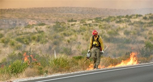 This image provided by the Pecos Zone Team 3 shows a firefighter lighting backfires along the road leading into Carlsbad Caverns National Park, N.M. on June 15, 2011. (AP Photo/Pecos Zone Team 3)