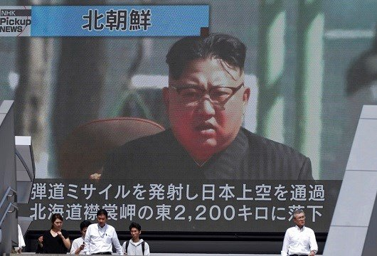 People walk past a public TV screen showing a file footage of North Korean leader Kim Jong Un during news on North's missile launch, in Tokyo.