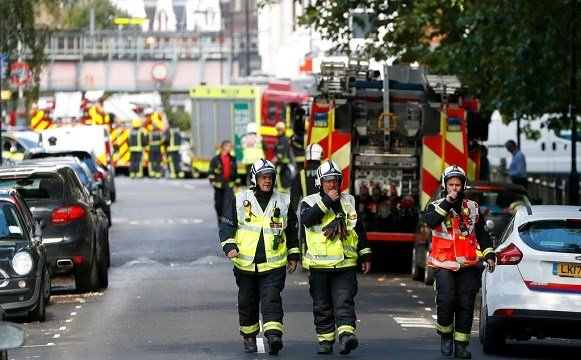 Fire brigade officers walk within a cordon near where an incident happened, that police say they are investigating as a terrorist attack, at Parsons Green subway station in London.