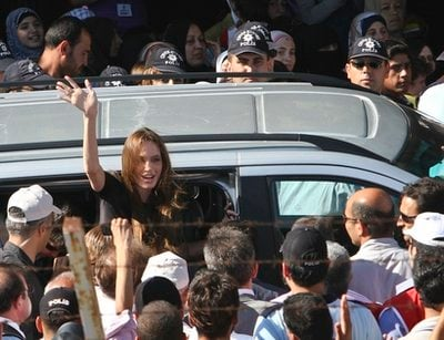 Angelina Jolie, Hollywood actress and goodwill ambassador for the U.N. High Commissioner for Refugees, UNHCR, waves as she exits a van surrounded by Syrian refugees at the Altinozu refugee camp, Turkey, near the Syrian border, Friday, June 17, 2011. U.N.
