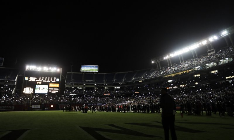 San Diego State players look on as fans hold lights from their cellphones during a stadium lighting delay in the second half of an NCAA college football game against Stanford Saturday, Sept. 16, 2017, in San Diego.