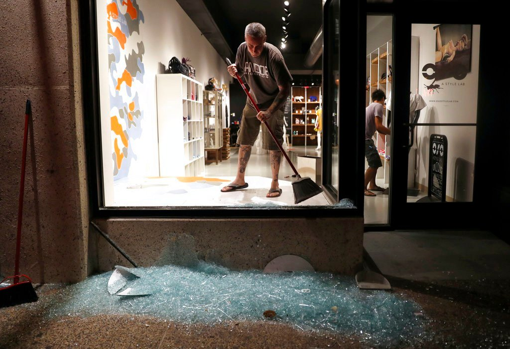 Scott McRoberts helps clean up broken glass after a violent crowd broke windows on many businesses after clashing with police Saturday, Sept. 16, 2017, in University City, Mo. (AP Photo/Jeff Roberson)