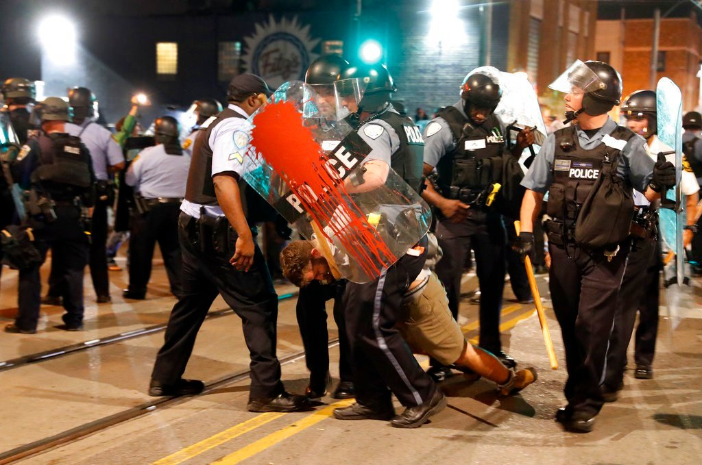Police arrest a man as they try to clear a violent crowd Saturday, Sept. 16, 2017, in University City, Mo. (AP Photo/Jeff Roberson)