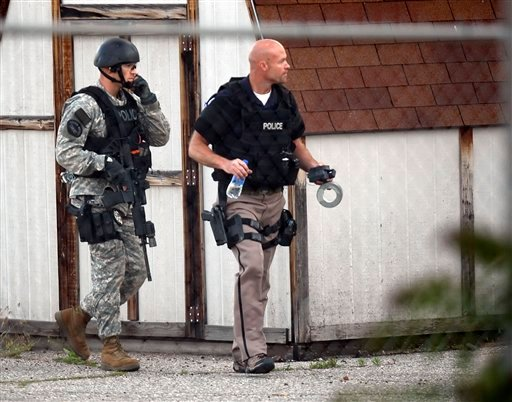 In this June 17, 2011 photo, officers approach the area as Ogden City Police respond to a hostage situation at the Western Colony Inn where a man holds a woman hostage, in Ogden, Utah.