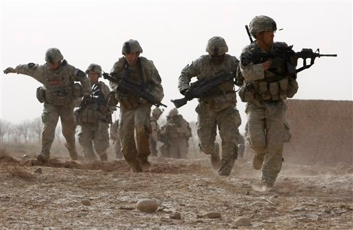 FILE - In a Feb. 14, 2010 file photo, a U.S. soldier returns fire as others run for cover during a firefight with insurgents in the Badula Qulp area, west of Lashkar Gah in Helmand province, southern Afghanistan.