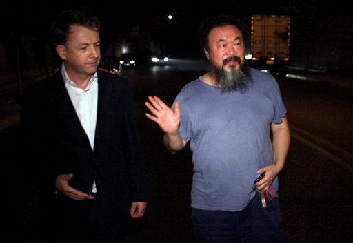 Activist artiste Ai Weiwei, declines to comment near an unidentified foreign journalist outside his home in Beijing, China, Wednesday, June 22, 2011.