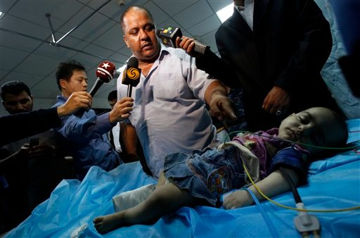 """In this photo taken on a government organized tour, Libyan official points at a girl identified by officials as """"Haneen"""" while he speaks to the media in hospital in Tripoli, Libya, on Sunday, June 5, 2011."""