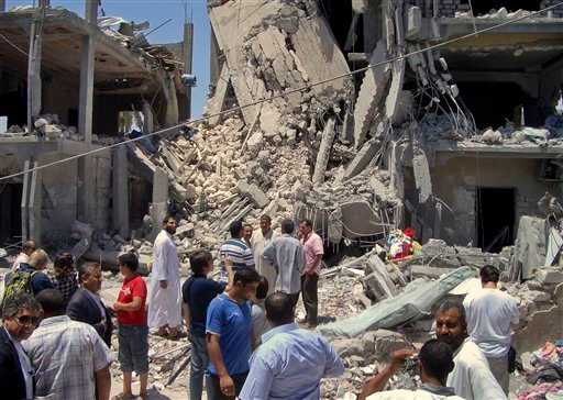 In this photo taken on a government-organized tour, members of the media and others examine the remains of a damaged residential building in Tripoli, Libya Sunday, June 19, 2011.