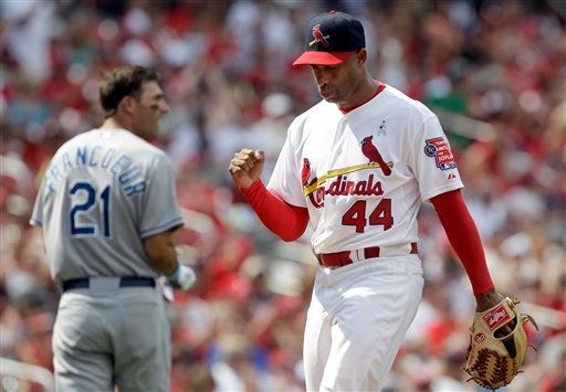 St. Louis Cardinals relief pitcher Miguel Batista, right, pumps his fist as he walks off the field after getting Kansas City Royals' Jeff Francoeur, left, to hit into an inning-ending double play Sunday, June 19, 2011.