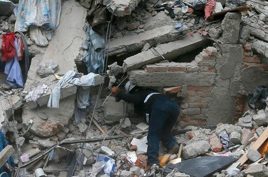 A construction worker searches a building that collapsed after an earthquake, in the Roma neighborhood of Mexico City.