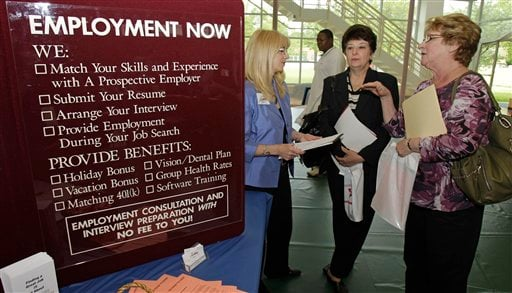 In this May 25, 2011 photo, Glynis Davies, left, from Hartman Personal Services, talks with job seekers Christine Marciante and Maxine Janke, right, at the Jobapalooza job fair in Painesville, Ohio. (AP Photo/Tony Dejak)