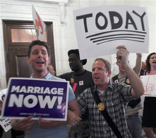Supporters for gay marriage carry signs and sing in a hallway outside a Republican conference room at the Capitol in Albany, N.Y., on Wednesday, June 22, 2011. (AP Photo/Mike Groll)