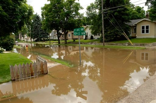 Water fills the streets in the Oak Park neighborhood of Minot, N.D. on Wednesday, June 22, 2011. As many as 10,000 people raced to evacuate Wednesday as water began spilling over Minot's levees. (AP Photo/Will Kincaid)