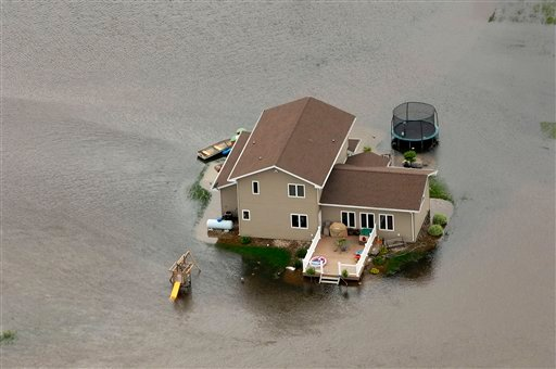 A home is surrounded by water near Minot, N,D. on Wednesday, June 22, 2011. (AP Photo/Will Kincaid)