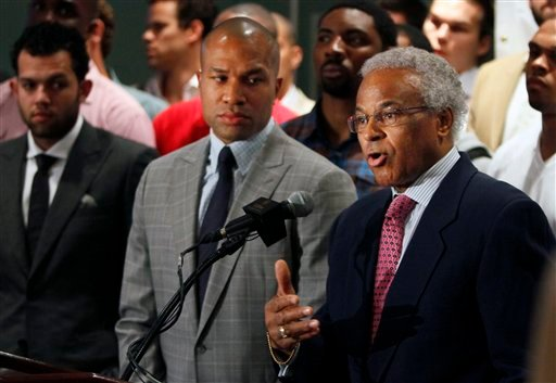 National Basketball Players Association union president Derek Fisher, of the Los Angles Lakers, listens as NBPA executive director Billy Hunter, right, speaks during a news conference, Thursday, June 23, 2011, with NBA players standing behind them.