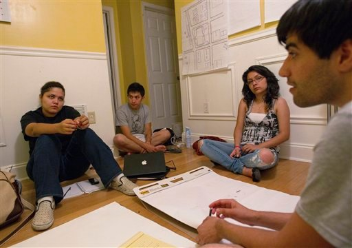 In a May 31, 2011 photo, Illegal immigrants Georgina Perez, left, Adam Kuranishi, second from left, and Dulce Guerrero, third from left, take part in a meeting organizing a rally with activist Mohammad Abdollahi, right.