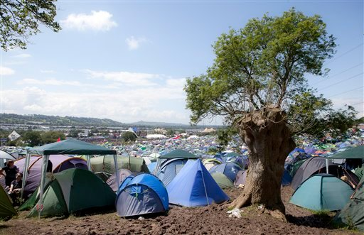 Yents stand in the mud overlooking the Pyramid stage ahead of the annual Glastonbury Music Festival, at Pilton, England, Thursday, June 23, 2011, as more of the 170,000 music fans expected to attend the sell-out festival arrived at the venue.