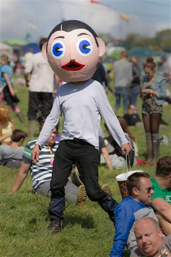 A man dressed as comedian and musician Frank Sidebottom walks through the main stage at Glastonbury Music Festival, Glastonbury, England, Thursday, June 23, 2011.