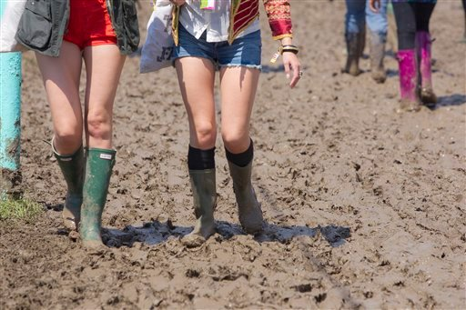 Festival-goers wearing wellington boots make their way through the mud ahead of the the annual Glastonbury Music Festival, at Pilton, England, Thursday, June 23, 2011, as more of the 170,000 music fans expected to attend the sell-out festival.