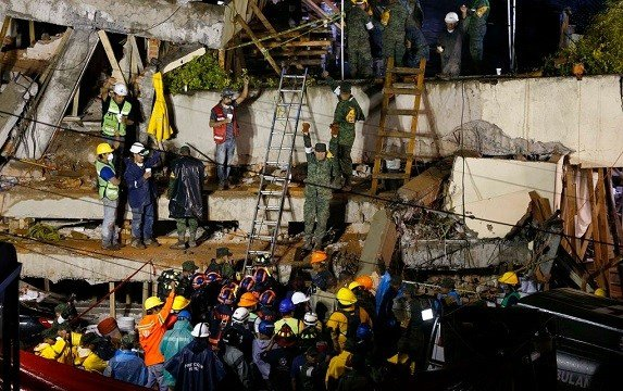 Rescue personnel work on the rescue of a trapped child at the collapsed Enrique Rebsamen primary schoool in Mexico City, Sept. 20, 2017.